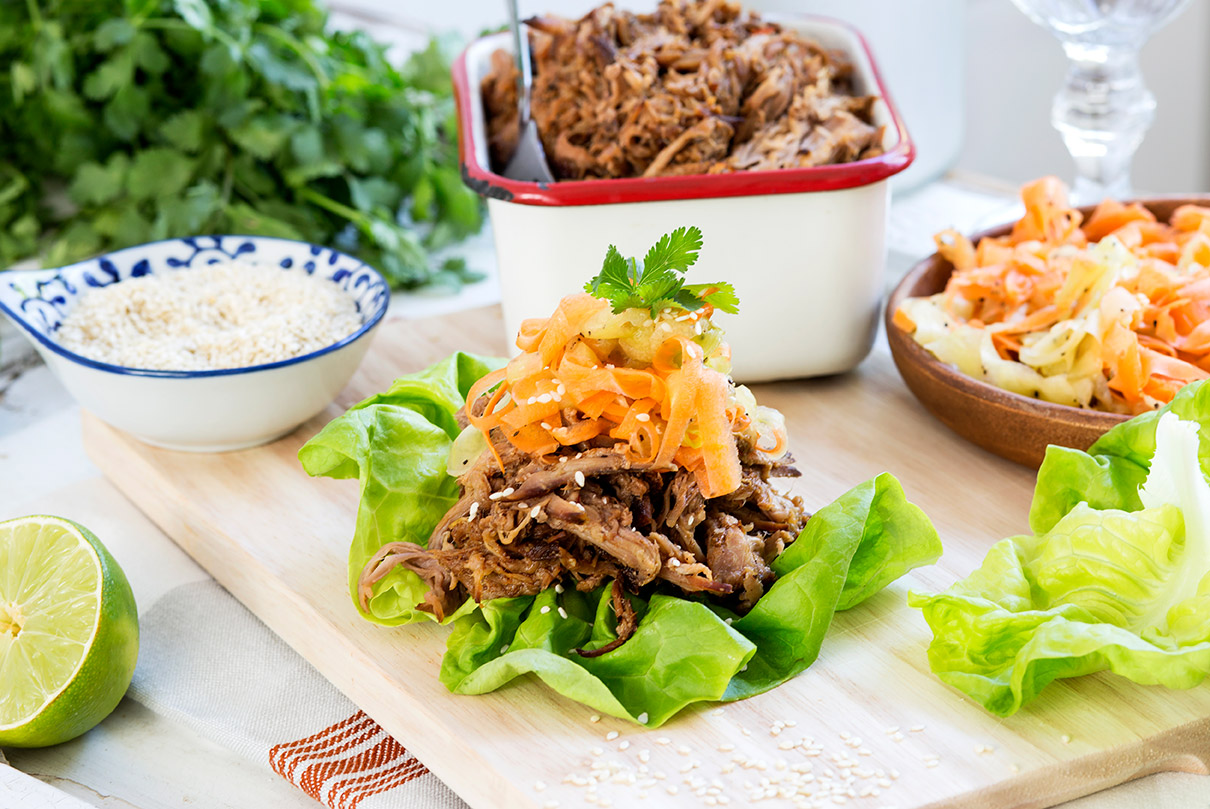 A board filled with slow cooked San-J Asian pulled pork with pickled vegetables on a bed of lettuce