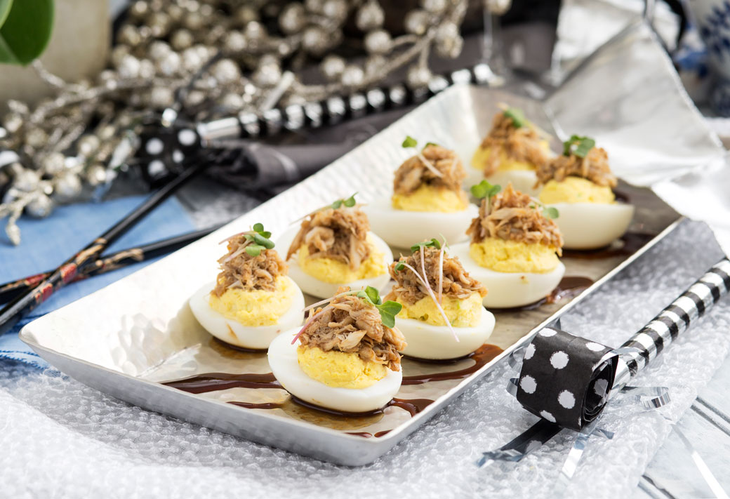 Hoisin Crab Deviled eggs on a plate smothered with San-J Soy Sauce