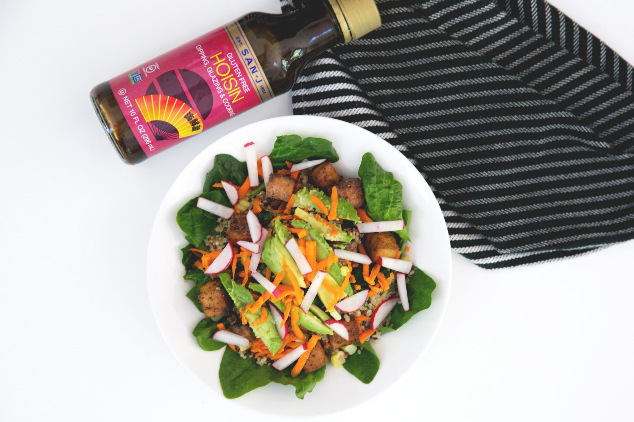 A bowl filled with hoisin grains on a table with a serviette and a bottle of hoisin san-j sauce