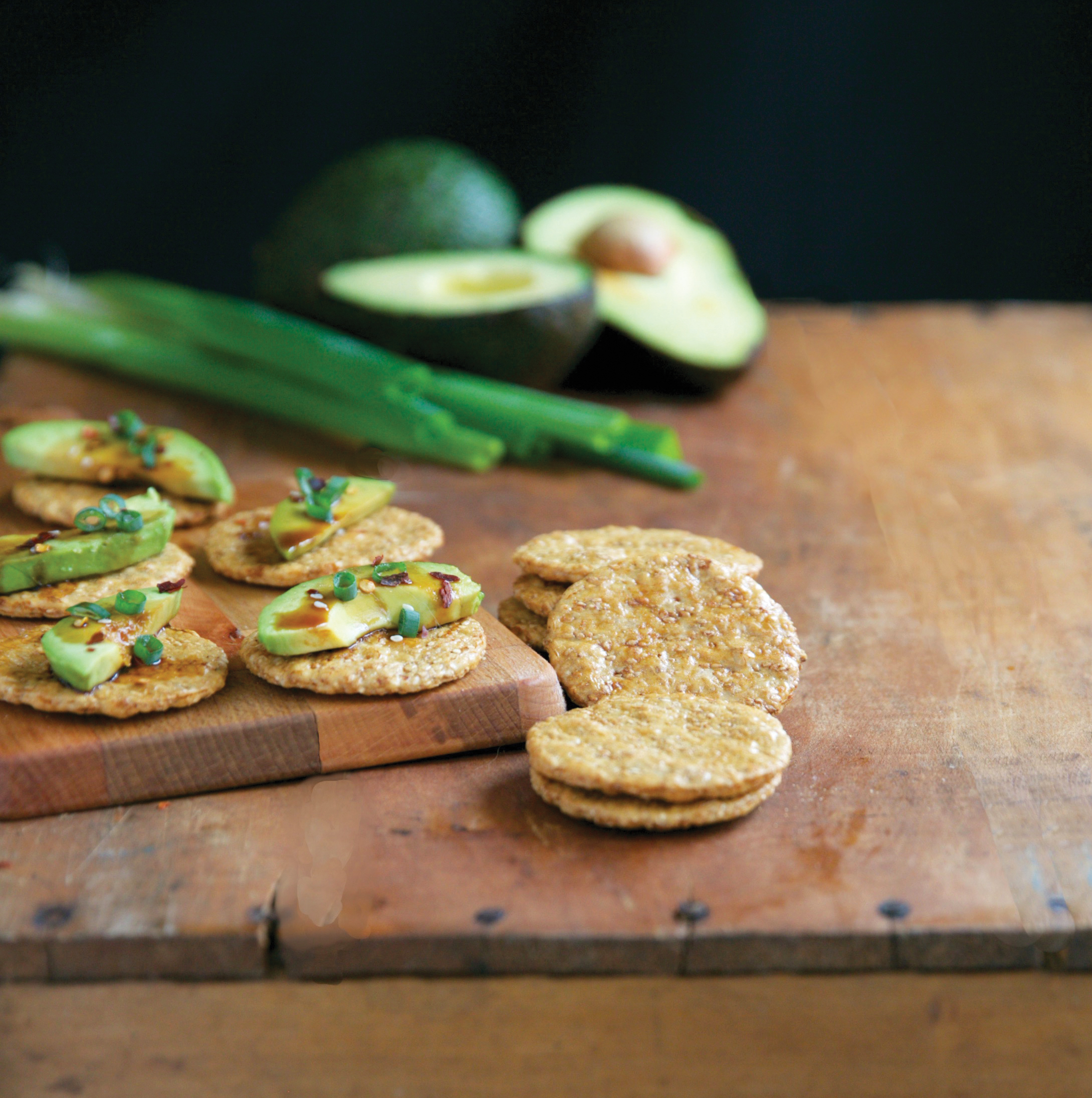 Avocado on crackers on a board by San-J