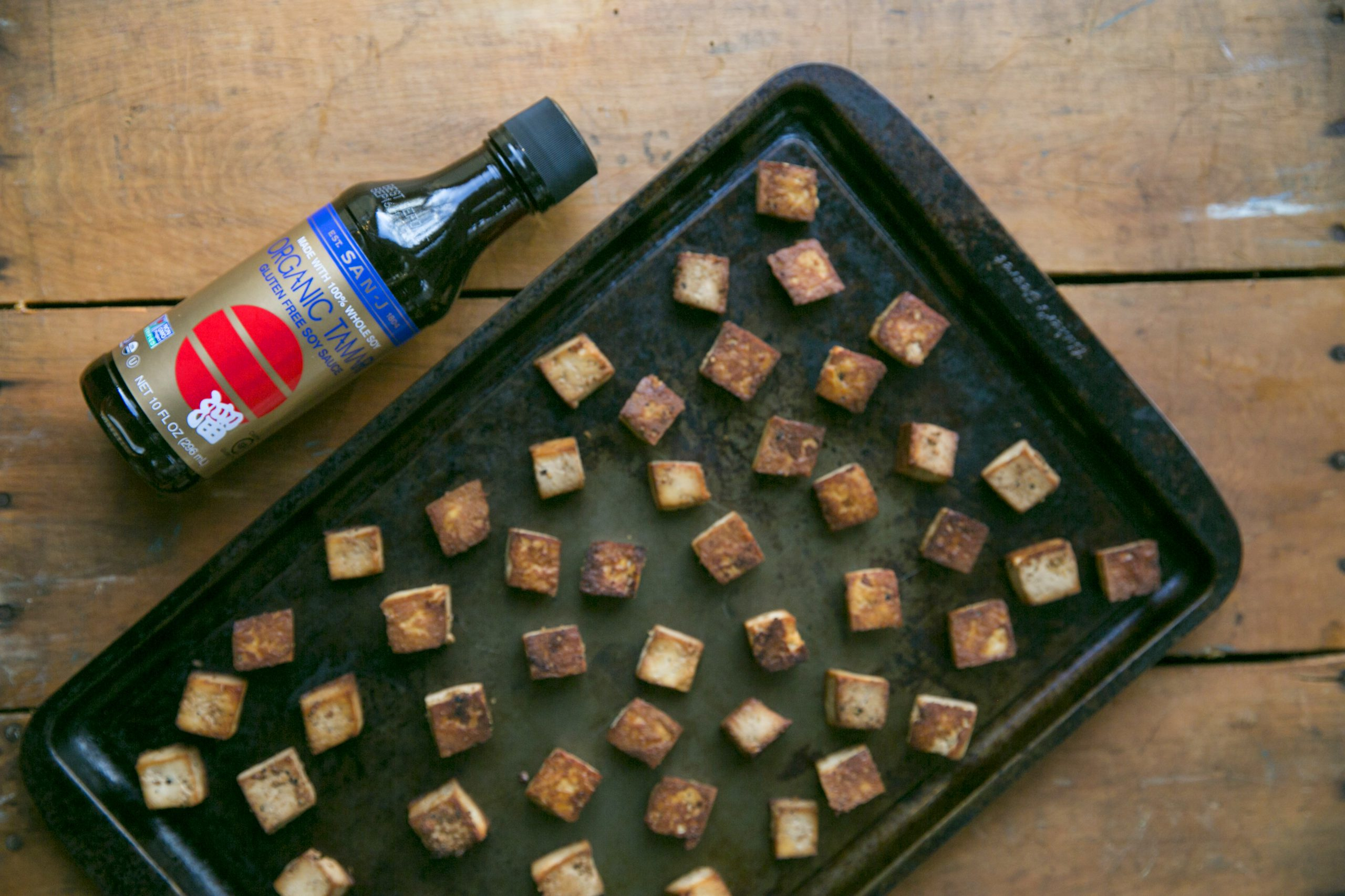 San-J organic tofu with in a baking tray with a bottle of organic tamari soy sauce by San-J