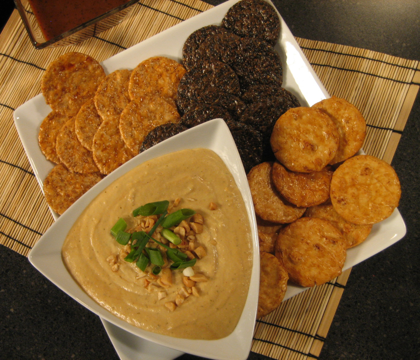 A platter of crackers with San-J Asian hummus in a bowl