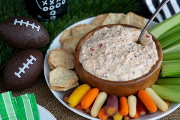 A dip bowl on a plate filled with San-J Hawaiian pimento cheese dip and vegetables