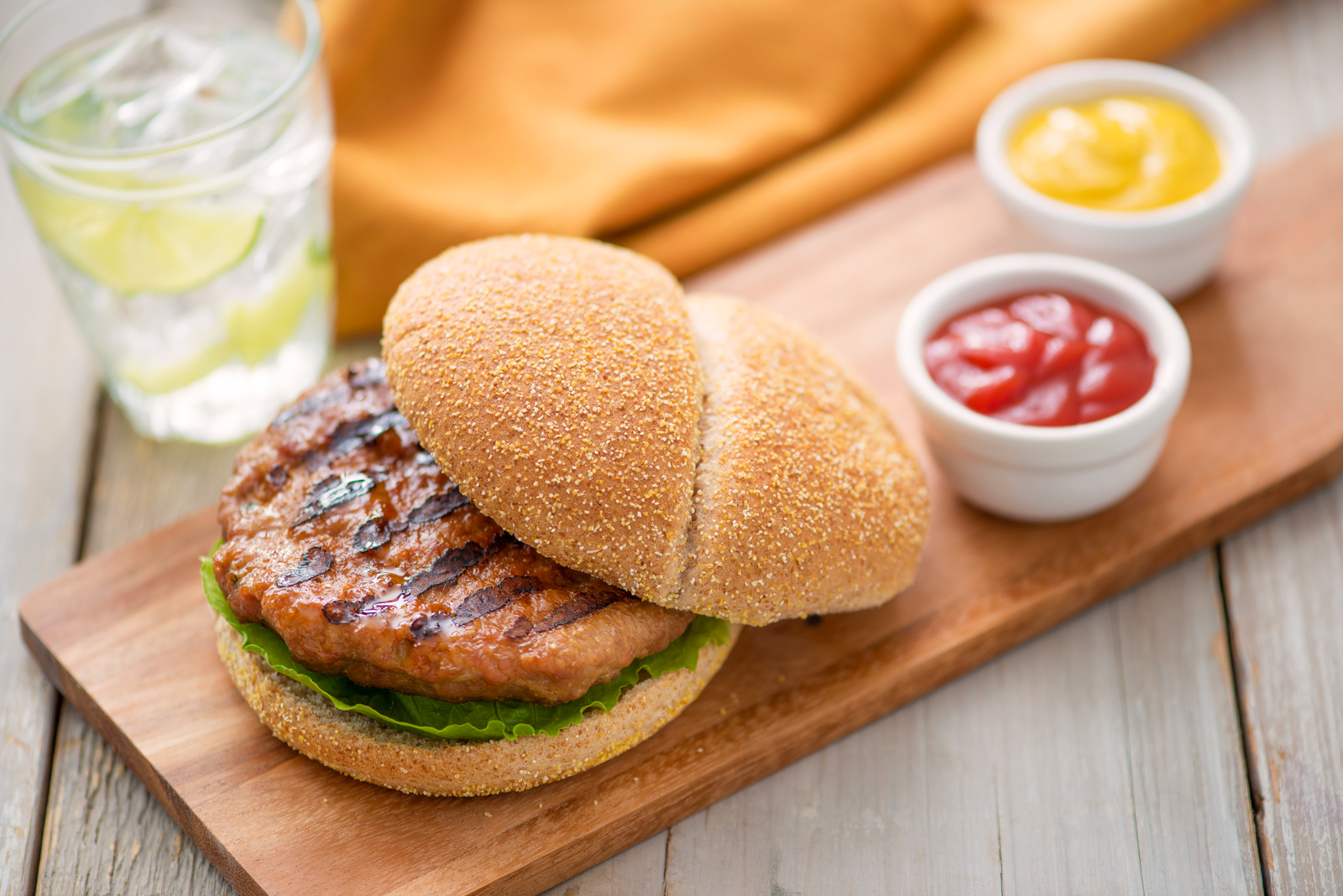 A board with a San-J lean and spicy miso turkey burger and dips