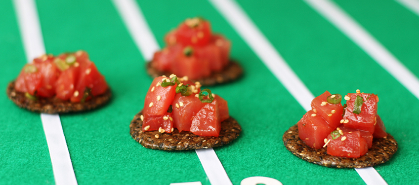 Four black sesame rice crackers topped with spicy ahi poke by San-J